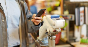 Mann zahlt mit Smartphone an Kasse im Supermarkt