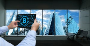 Cryptocurrency, blockchain and bitcoin concept.Distributed ledger technology.Man holding tablet , block chain and bitcoin icons with smart building background. Window showing smart building background