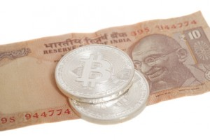 Silver bitcoin coins on Indian Ten Rupee isolated on white