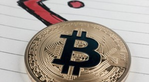 Cryptocurrency physical gold bitcoin coin and red arrow in notebook.