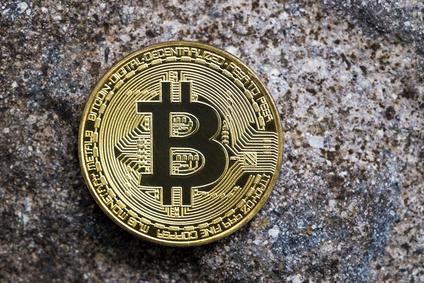 Golden bitcoin on stone surface.