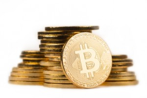 golden bitcoin in front of a pile of golden metallic coins on white