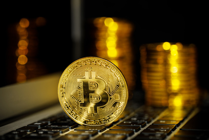 Bitcoin. Physical Bitcoin on laptop. Golden coin with bitcoin symbol on notebook keyboard. Digital currency
